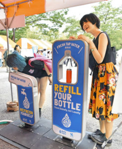A woman poses with a sign encouraging refilling water bottles with Tokyo tap water. Source: Tokyo Shimbun